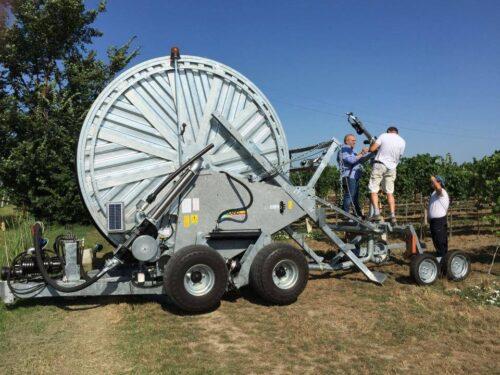 Un paio di uomini stanno regolando il getto di un irrigatore