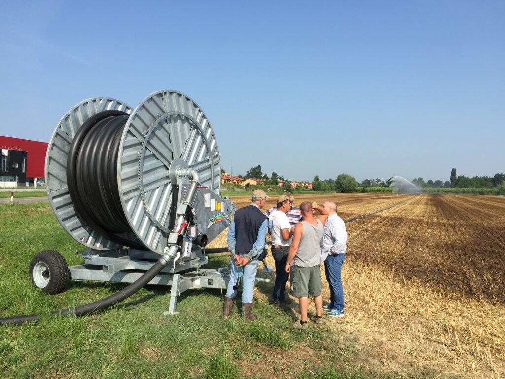Serie di irrigatori in azione in un campo, in primo piano un irrigatore ed un gruppo di persone, sullo sfondo un irrigatore con il suo getto d'acqua